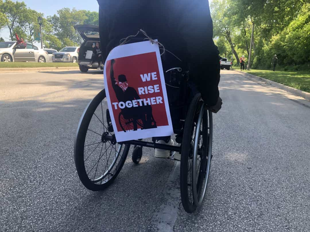 a person in a wheelchair facing away with a poster on the back of the chair saying We Rise Together