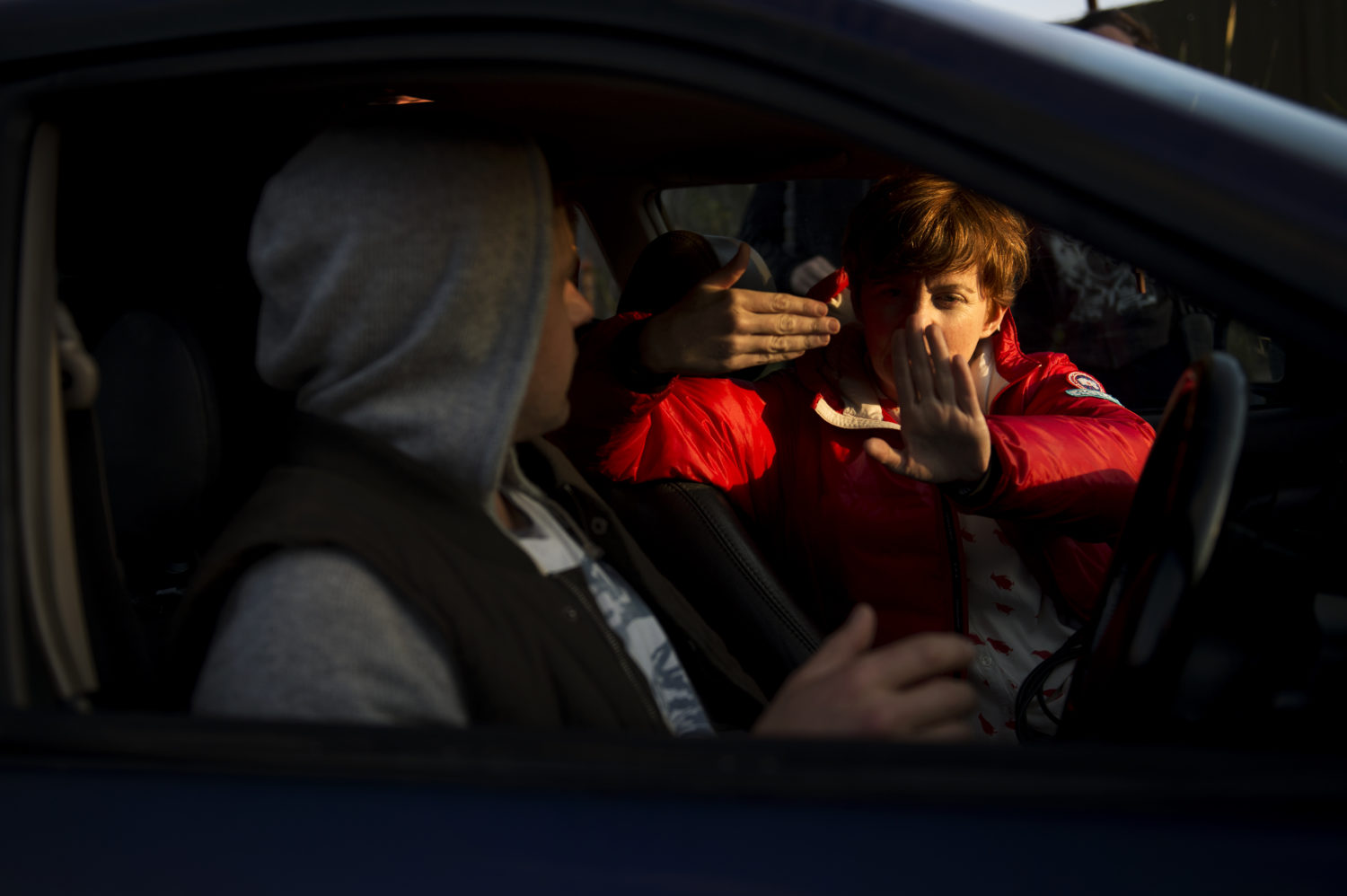 Sofya in a bright red jacket in the passenger seat of a car, giving direction to an actor in a hoodie behind the wheel.