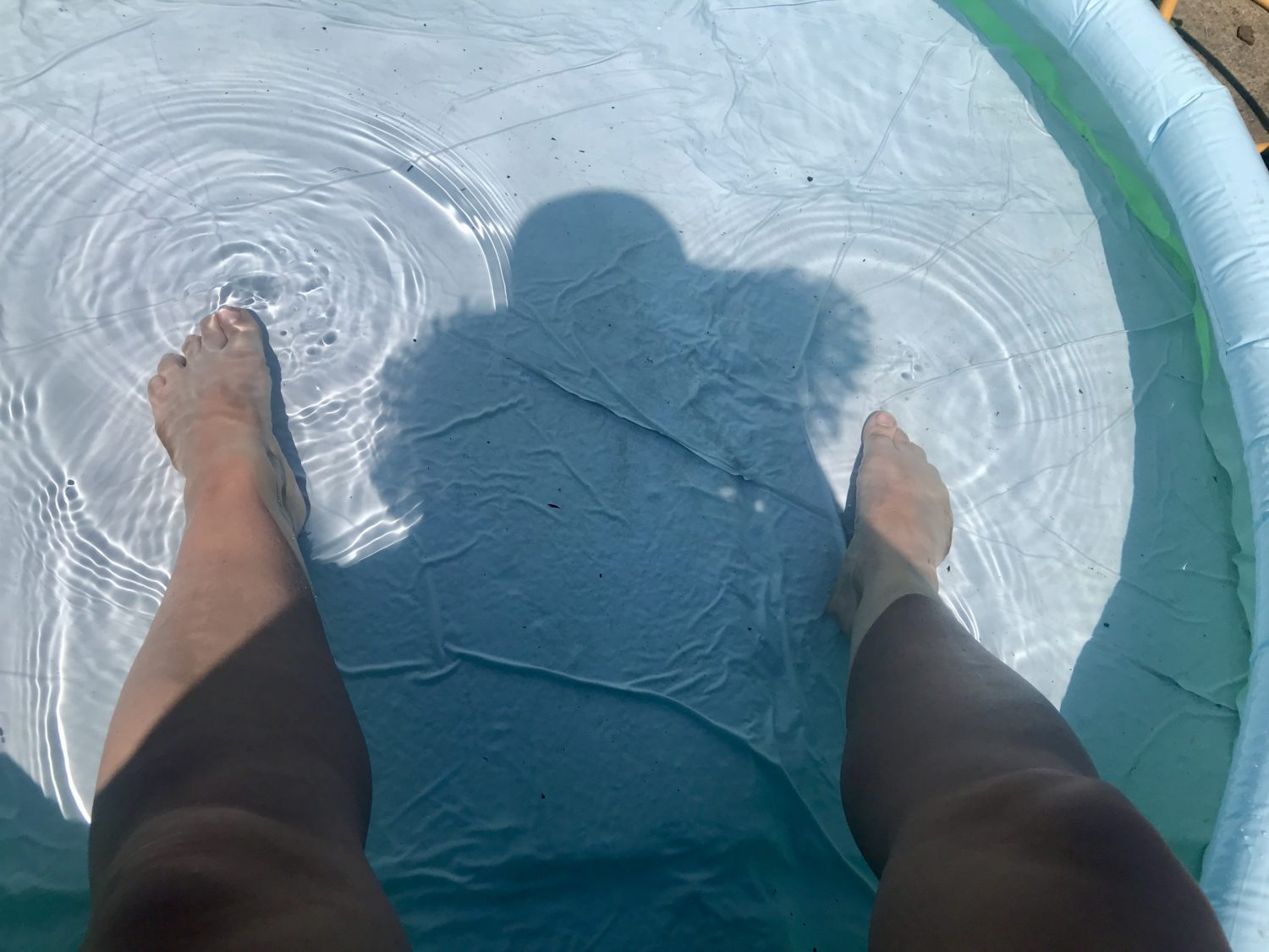 A picture of legs in a paddling pool and a shadow of a person with a hat reflected in the pool.