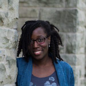 Une femme noire avec des cheveux noirs mi-longs fait face à la caméra et porte une robe bleue, une veste en denim et des lunettes. Elle sourit.