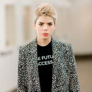 Une femme avec des cheveux teints blonds fait face vers l'avant et porte une veste imprimé léopard et du rouge à lèvres