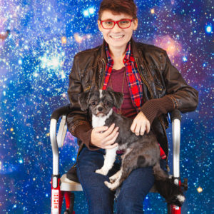 A person wearing a red shirt and brown jacket sits on a chair smiling with a dog on their lap against a vibrant blue galactic backdrop.