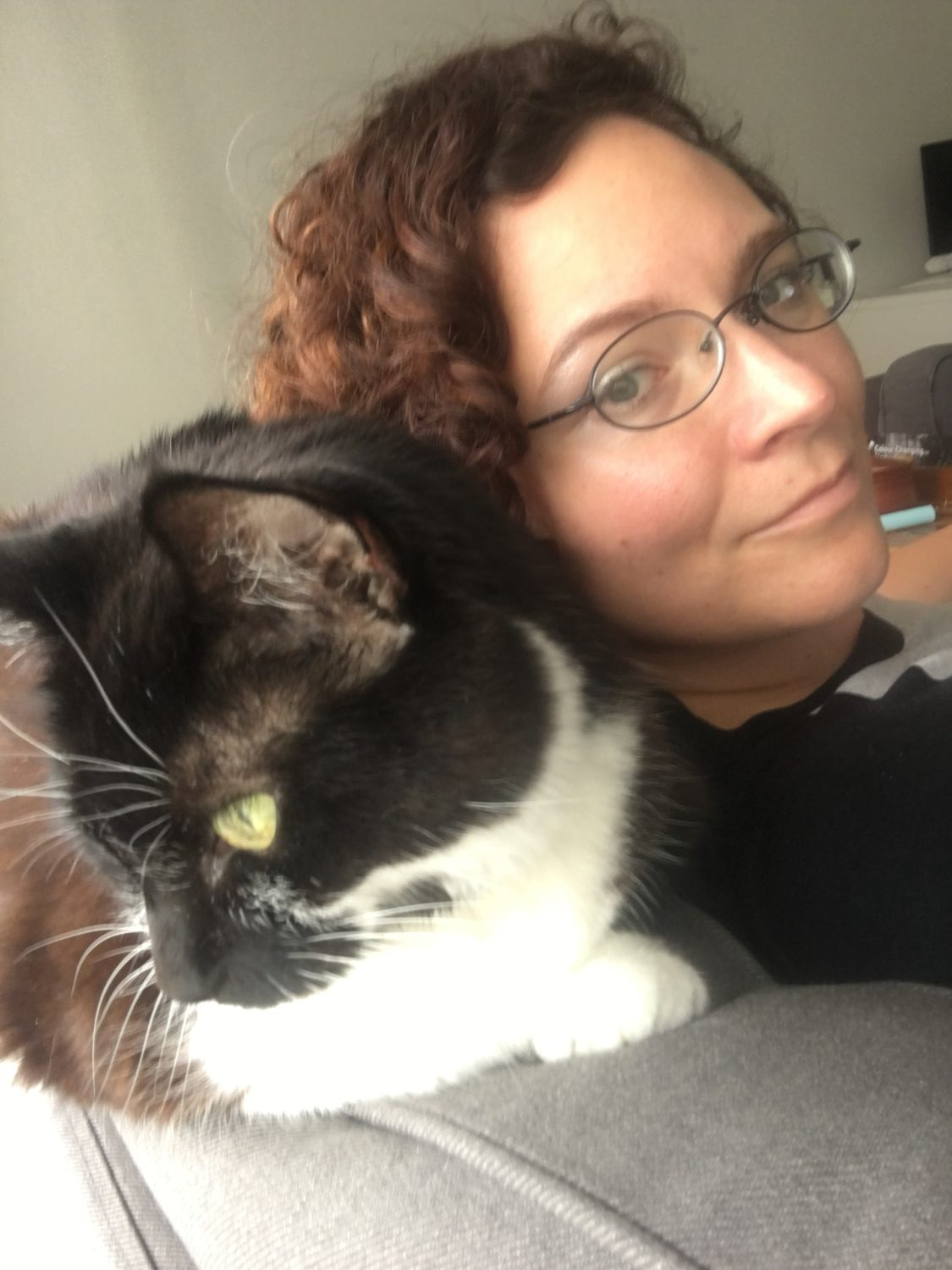 A photograph of a white woman with curly brown hair looks fondly over her shoulder at Finn, a tuxedo cat