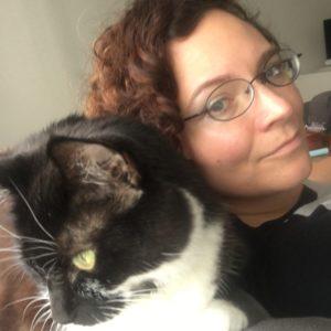 Une femme blanche avec des cheveux bruns bouclés regarde par-dessus son épaule vers Finn, un chat noir et blanc