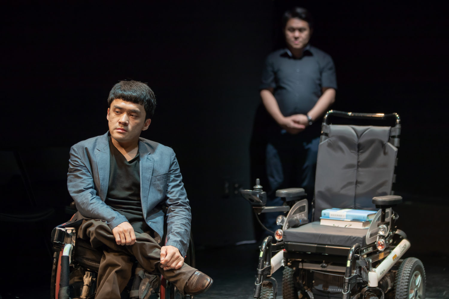 shows two men in a dramatic scene, one in front of the other, one in a wheelchair, the other standing behind.