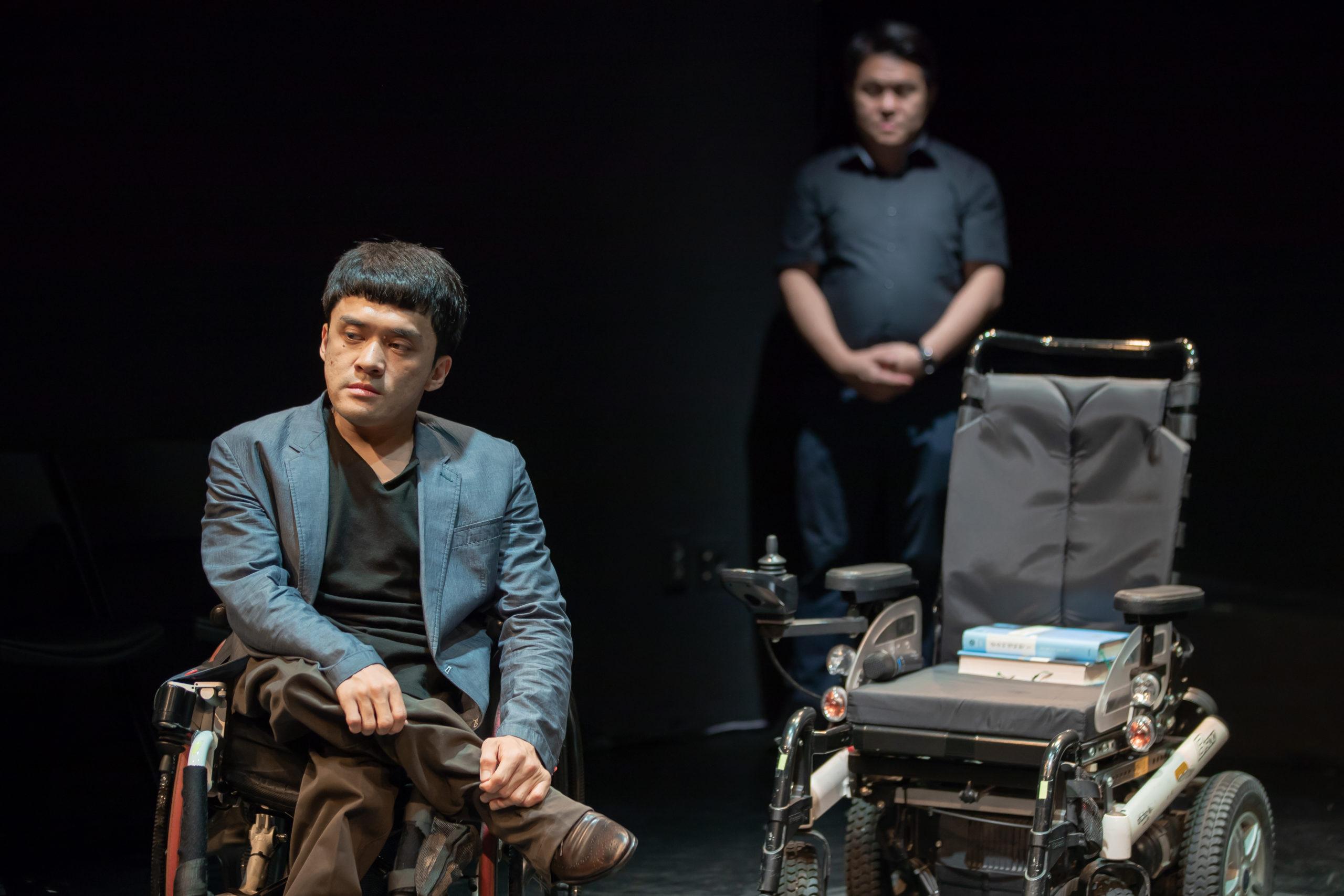 Deux hommes jouant une scène dramatique sur scène. L'un est en fauteuil roulant en premier plan, et l'autre est debout derrière lui.