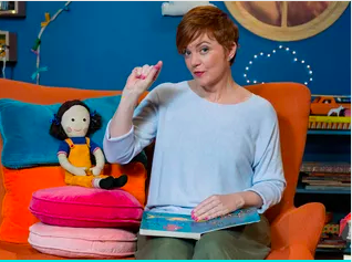 Sofya on an orange sofa, presenting live on Play School, for ABC, Australia