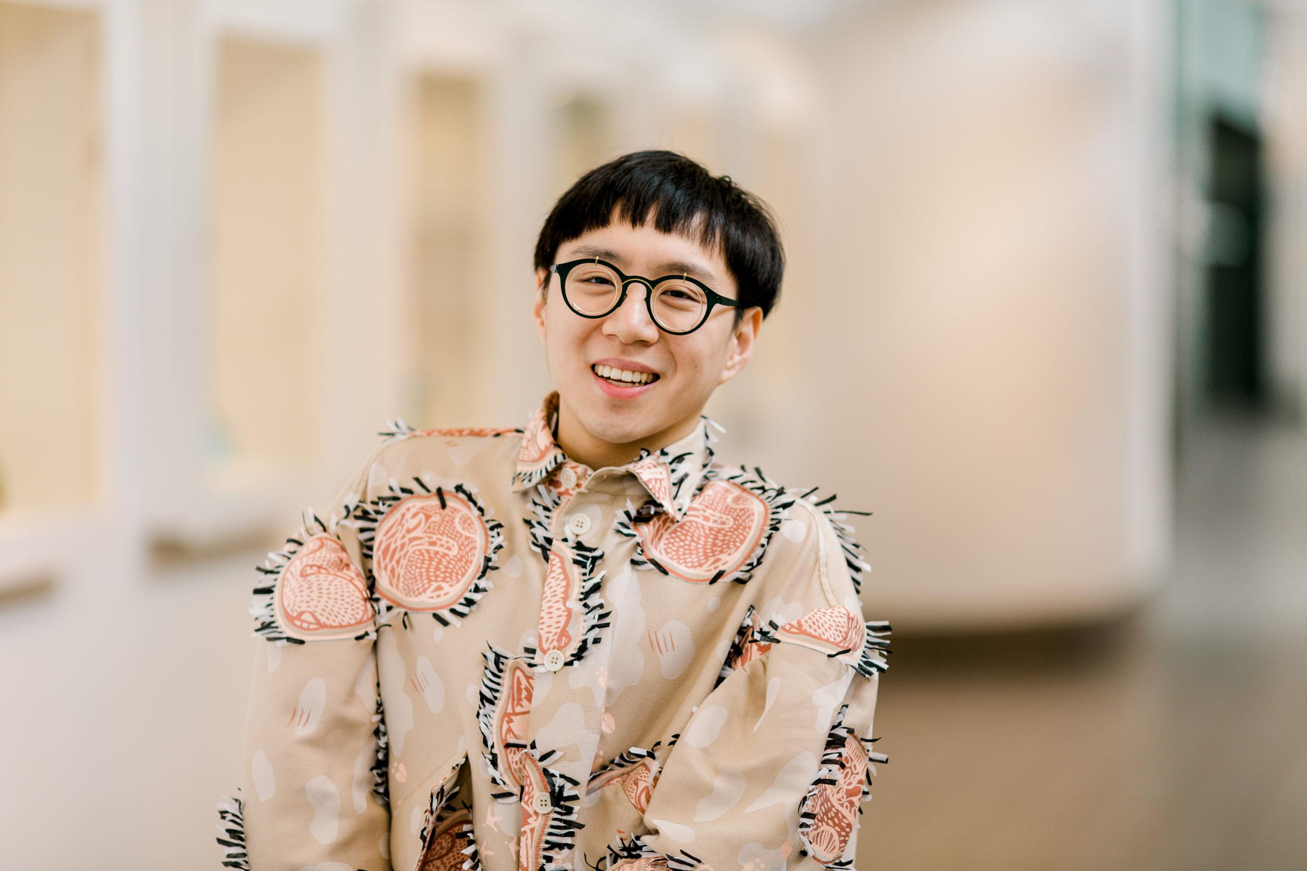 Portrait en buste d'une personne portant une chemise aux couleurs vives et des lunettes