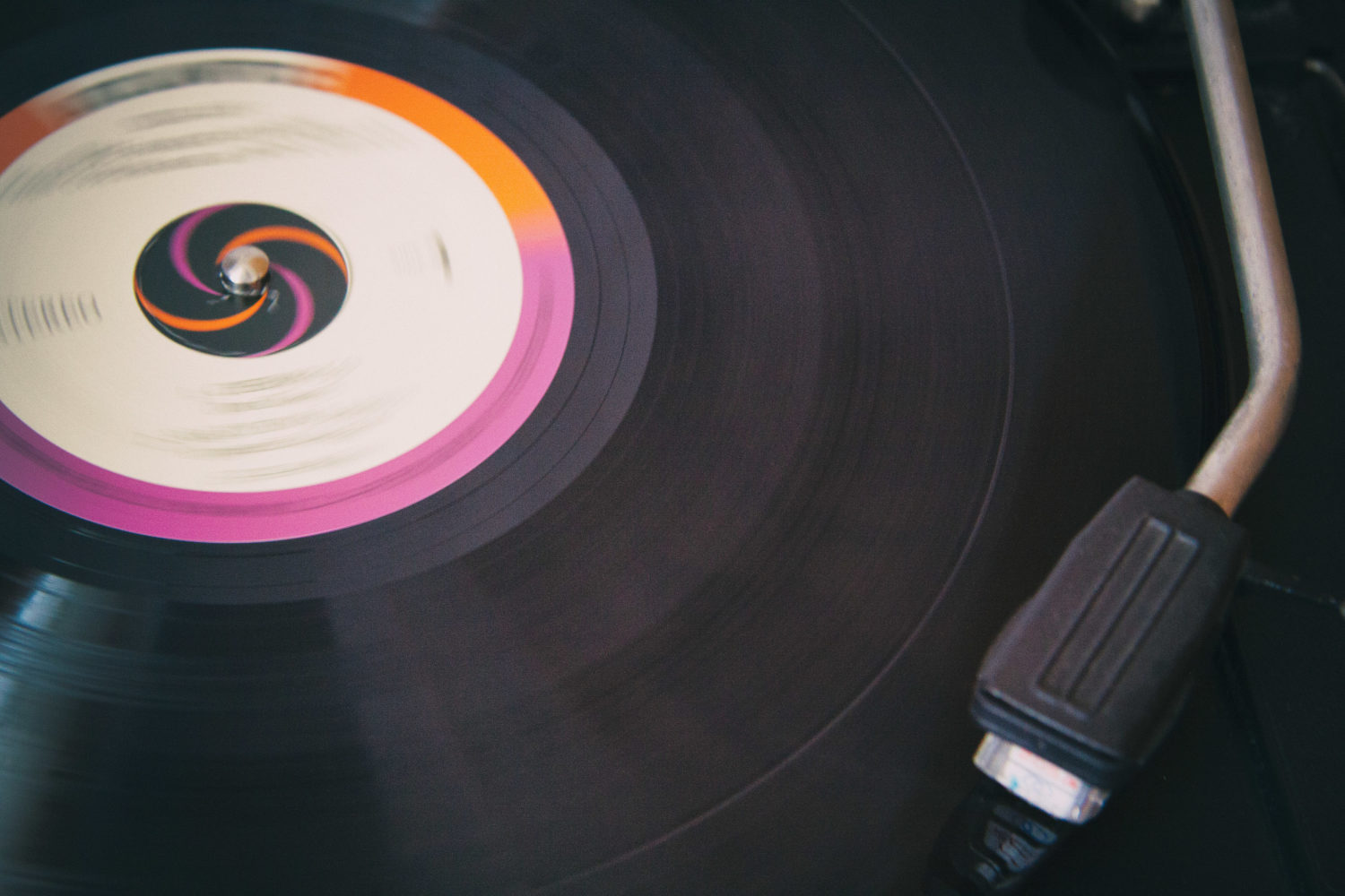 A needle sat upon a vinyl record - it's centre decorated with a fuscia pink and orange design.