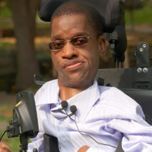 a picture of B.Paul Tshuma in a wheelchair, wearing a white shirt, wearing glasses