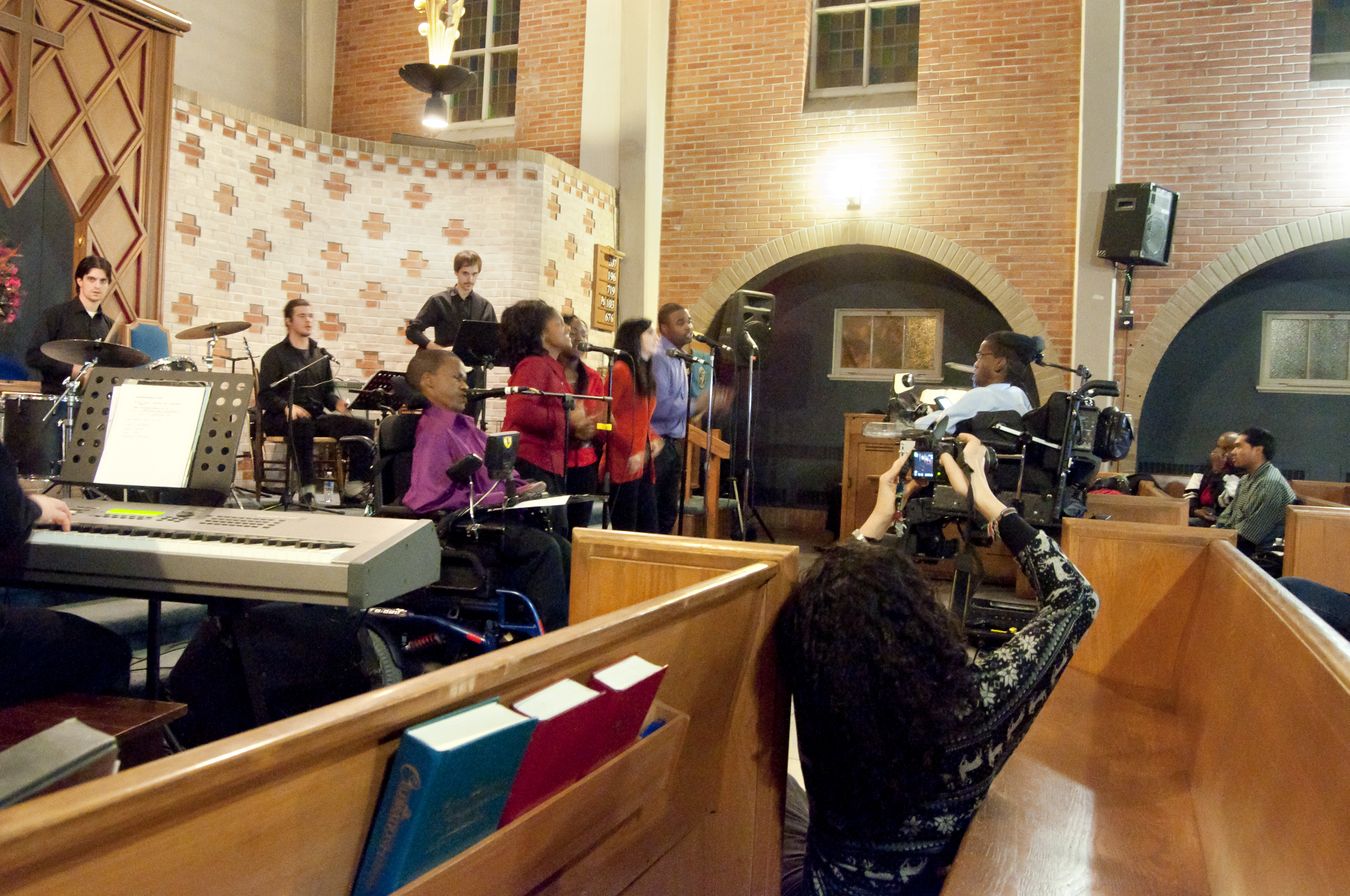B. Paul Tshuma conducts the choir from his chair in a church setting. There is a band playing instruments behind the choir.