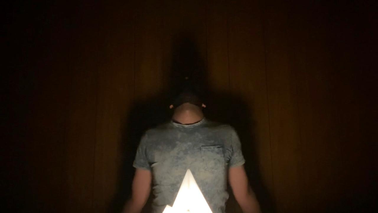 Connor est assis devant une lumière piquante d'un blanc éclatant, la tête tournée vers le haut et les bras à ses côtés. Son ombre est projetée contre le mur derrière. Il porte une simple chemise à manches courtes teinte à l'acide bleu